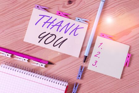 Conceptual hand writing showing Thank You. Concept meaning polite expression used when acknowledging gift service compliment Colored crumpled papers wooden floor background clothespin