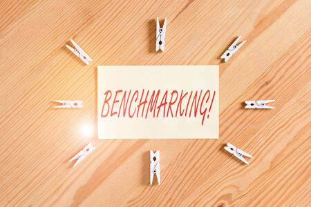 Text sign showing Benchmarking. Business photo showcasing evaluate something by comparison with standard or scores Colored clothespin papers empty reminder wooden floor background office