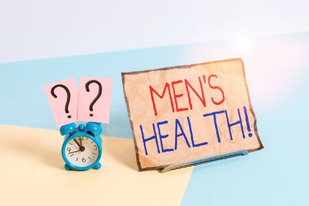 Writing note showing Men S Health. Business concept for state of complete physical mental and social well being by analysis Alarm clock beside a Paper sheet placed on pastel backdrop