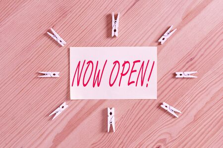 Text sign showing Now Open. Business photo showcasing leave door or windows not closed or barred at this current time Colored clothespin papers empty reminder wooden floor background office