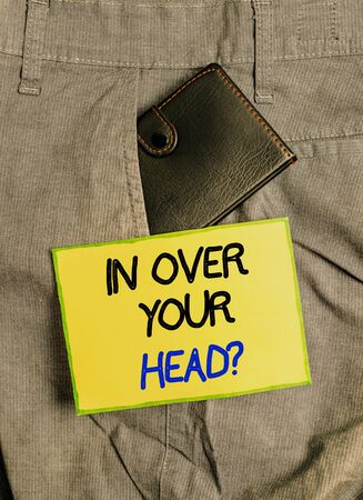 Handwriting text writing In Over Your Head question. Conceptual photo To be involved in a difficult situation problem Small little wallet inside man trousers front pocket near notation paper
