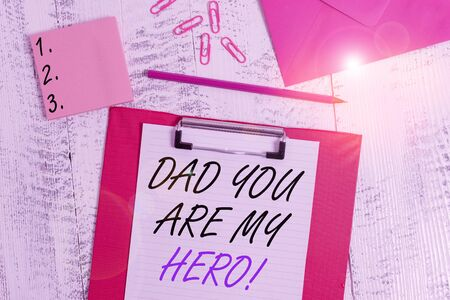 Writing note showing Dad You Are My Hero. Business concept for Admiration for your father love feelings compliment Clipboard paper sheet pencil envelope clips notepad wooden background 写真素材