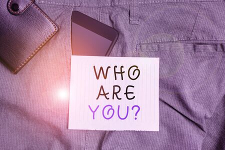 Conceptual hand writing showing Who Are You question. Concept meaning Identify yourself description demonstrating characteristics Smartphone device inside trousers front pocket with wallet