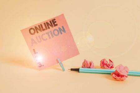 Text sign showing Online Auction. Business photo showcasing process of buying and selling goods or services online Plain note paper and stationary placed above soft pastel colour backdrop