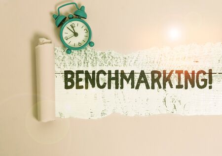 Text sign showing Benchmarking. Business photo showcasing evaluate something by comparison with standard or scores Alarm clock and torn cardboard placed above a wooden classic table backdrop