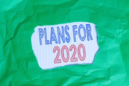 Writing note showing Plans For 2020. Business concept for an intention or decision about what one is going to do Green crumpled colored paper sheet torn colorful background