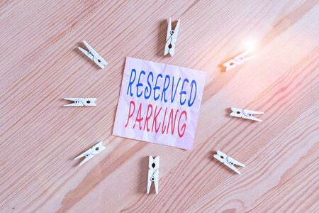 Writing note showing Reserved Parking. Business concept for parking spaces that are reserved for specific individuals Colored clothespin papers empty reminder wooden floor background office Stockfoto
