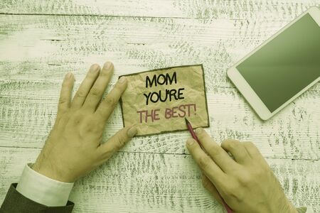 Word writing text Mom You re are The Best. Business photo showcasing Appreciation for your mother love feelings compliment Hand hold note paper near writing equipment and modern smartphone device Banco de Imagens