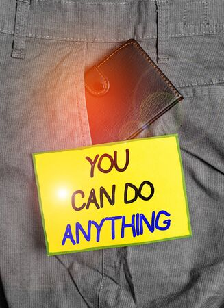 Handwriting text writing You Can Do Anything. Conceptual photo Motivation for doing something Believe in yourself Small little wallet inside man trousers front pocket near notation paper 스톡 콘텐츠