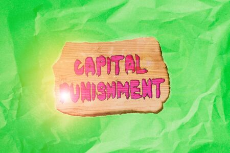 Word writing text Capital Punishment. Business photo showcasing authorized killing of someone as punishment for a crime Green crumpled ripped colored paper sheet centre torn colorful background
