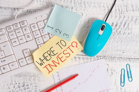 Writing note showing Where To Invest Question. Business concept for asking where put money into financial schemes or shares Writing equipments and computer stuff placed on wooden table Banco de Imagens