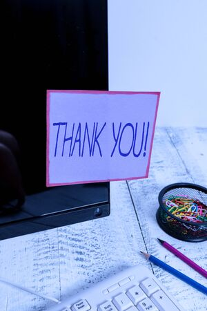 Handwriting text writing Thank You. Conceptual photo polite expression used when acknowledging gift service compliment Note paper taped to black computer screen near keyboard and stationary