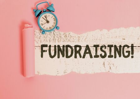 Text sign showing Fundraising. Business photo showcasing seeking to generate financial support for charity or cause Alarm clock and torn cardboard placed above a wooden classic table backdrop