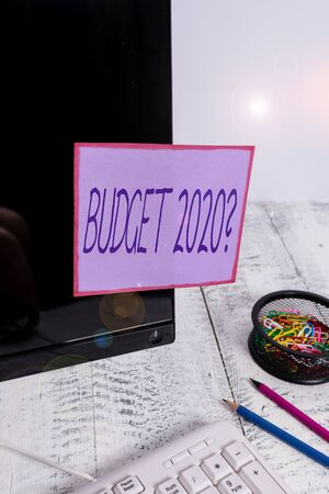 Handwriting text writing Budget 2020 Question. Conceptual photo estimate of income and expenditure for next year Note paper taped to black computer screen near keyboard and stationary
