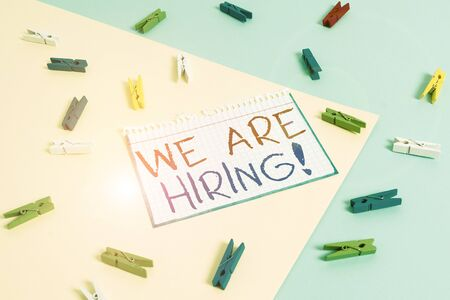 Writing note showing We Are Hiring. Business concept for recently you employ someone or pay someone to do particular job Colored clothespin paper reminder with yellow blue background Stock Photo