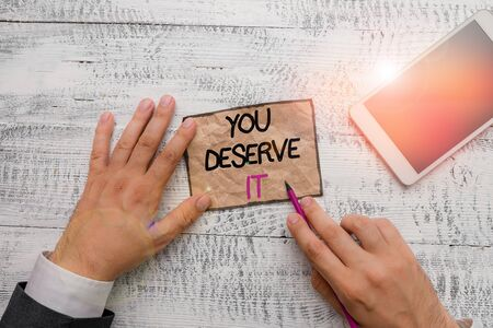 Word writing text You Deserve It. Business photo showcasing Reward for something well done Deserve Recognition award Hand hold note paper near writing equipment and modern smartphone device
