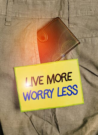 Handwriting text writing Live More Worry Less. Conceptual photo Have a good attitude motivation be careless enjoy life Small little wallet inside man trousers front pocket near notation paper