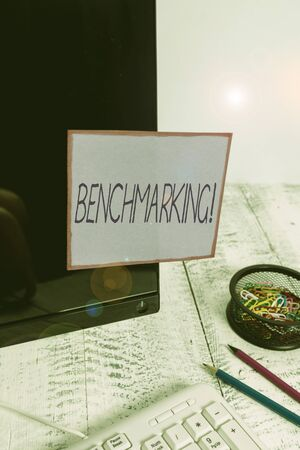 Handwriting text writing Benchmarking. Conceptual photo evaluate something by comparison with standard or scores Note paper taped to black computer screen near keyboard and stationary