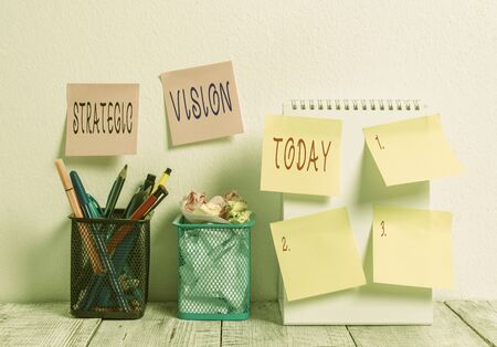Word writing text Strategic Vision. Business photo showcasing clarifies the direction the organisation needs to move 6 Sticky Notes on Wall Open Spiral Notebook 2 Pencil Pots on Work Desk