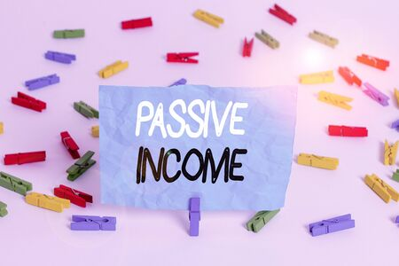 Handwriting text writing Passive Income. Conceptual photo the earnings derived from a rental property and others Colored clothespin papers empty reminder white floor background office
