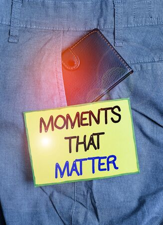 Handwriting text writing Moments That Matter. Conceptual photo Meaningful positive happy memorable important times Small little wallet inside man trousers front pocket near notation paper