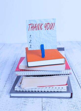Conceptual hand writing showing Thank You. Concept meaning polite expression used when acknowledging gift service compliment pile stacked books notebook pin color reminder white wooden