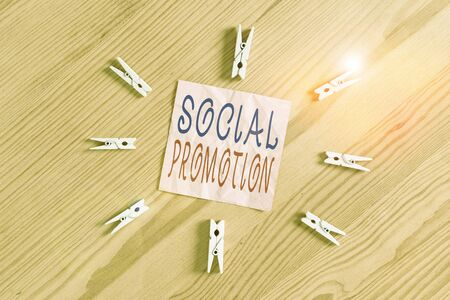 Writing note showing Social Promotion. Business concept for advancing students to the next grade to be with their peers Colored clothespin papers empty reminder wooden floor background office