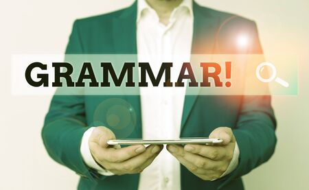 Word writing text Grammar. Business photo showcasing whole system structure language syntax and morphology Man in the blue suite and white shirt holds mobile phone in the hand
