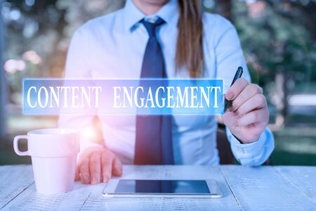 Conceptual hand writing showing Content Engagement. Concept meaning action a user takes on a given piece of content Female business person sitting and holding mobile phone