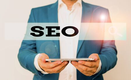 Word writing text Seo. Business photo showcasing incredibly effective way to market your near business online Man in the blue suite and white shirt holds mobile phone in the hand