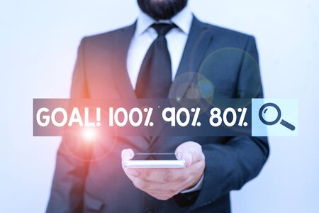 Writing note showing Goal 100 90 80. Business concept for Percentage of your objectives fulfilment success level Male human wear formal work suit hold smartphone using hand