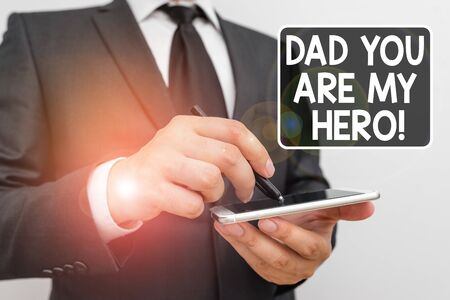 Writing note showing Dad You Are My Hero. Business concept for Admiration for your father love feelings compliment Male human wear formal work suit hold smartphone using hand