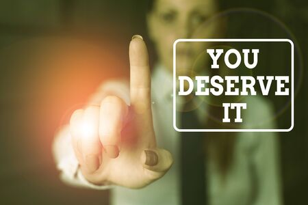 Conceptual hand writing showing You Deserve It. Concept meaning Reward for something well done Deserve Recognition award Woman in the background pointing with finger in empty space Stock fotó