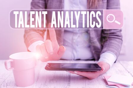 Handwriting text Talent Analytics. Conceptual photo data mining and business analytics technique to talent data Business woman sitting with mobile phone and cup of coffee on the table