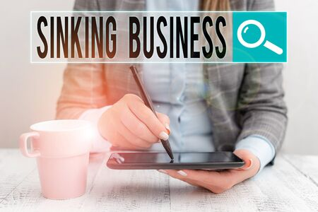 Conceptual hand writing showing Sinking Business. Concept meaning the company or other organization that is failing Business woman sitting with mobile phone and cup of coffee Stok Fotoğraf