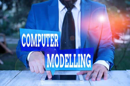 Word writing text Computer Modelling. Business photo showcasing using a computer to make a model of a plan or design Businessman in blue suite with a tie holds lap top in hands