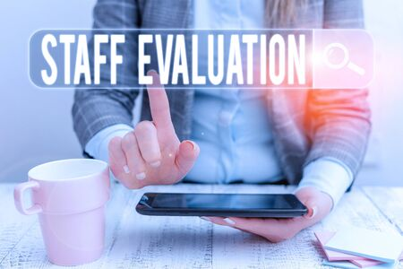 Handwriting text Staff Evaluation. Conceptual photo assessment and review of a worker s is job perforanalysisce Business woman sitting with mobile phone and cup of coffee on the table