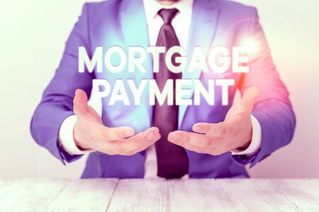 Conceptual hand writing showing Mortgage Payment. Concept meaning periodic amount paid to a holder for repayment of a loan Man holds empty paper with copy space in front of him Space Stok Fotoğraf