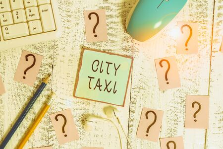 Word writing text City Taxi. Business photo showcasing type of vehicle for hire with a driver often for a nonshared ride Writing tools, computer stuff and scribbled paper on top of wooden table