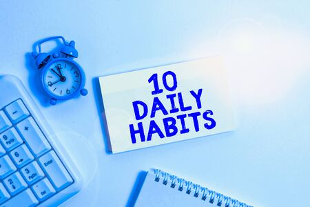 Conceptual hand writing showing 10 Daily Habits. Concept meaning Healthy routine lifestyle Good nutrition Exercises Keyboard with empty note paper and pencil white background