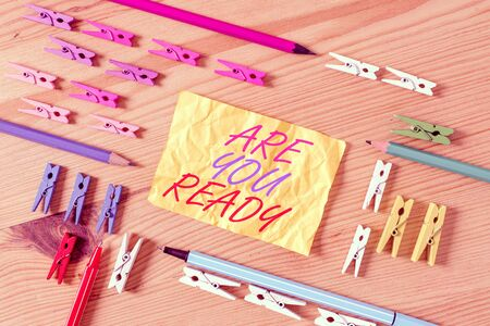 Text sign showing Are You Ready. Business photo showcasing Alertness Preparedness Urgency Game Start Hurry Wide awake Colored clothespin papers empty reminder wooden floor background office
