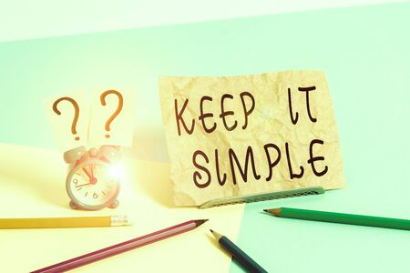 Conceptual hand writing showing Keep It Simple. Concept meaning Remain in the simple place or position not complicated Mini size alarm clock beside stationary on pastel backdrop