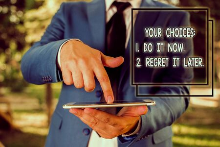 Conceptual hand writing showing Your Choices 1 Do It Now 2 Regret It Later. Concept meaning Think first before deciding Businessman in blue suite with a tie holds lap top in hands