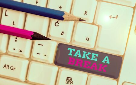 Conceptual hand writing showing Take A Break. Concept meaning Resting Stop doing something recreation time get out of work White pc keyboard with note paper above the white background