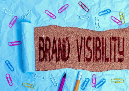 Conceptual hand writing showing Brand Visibility. Concept meaning frequency at which showing see your brand in search results Stationary and torn cardboard on a wooden classic table backdrop