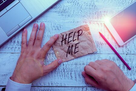 Writing note showing Help Me. Business concept for Asking someone to assist you Shouting for it Teamwork Volunteer Hand hold note paper near writing equipment and smartphone