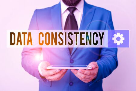 Text sign showing Data Consistency. Business photo text data values are the same for all instances of application Businessman in blue suite with a tie holds lap top in hands