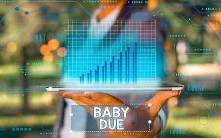 Escritura de texto Word Baby Due. Exhibición fotográfica de negocios a punto de nacer bajo compromiso en cuanto al tiempo que se espera que esté listo Foto de archivo