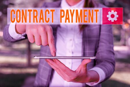 Handwriting text writing Contract Payment. Conceptual photo payments made by payer to the payee as per agreement terms Outdoor scene with business woman holds lap top with touch screen