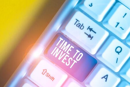 Conceptual hand writing showing Time To Invest. Concept meaning Creation of capital capable of producing other goods White pc keyboard with note paper above the white background Banco de Imagens